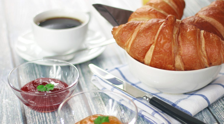 Frühstück mit Marmelade, Croissants und Kaffee